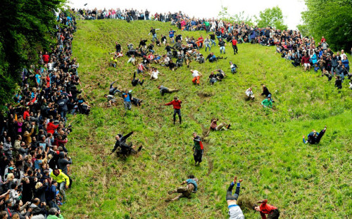 People rolling on a hill